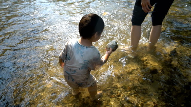 baby boy and mother playing together in small creek. - uncultivated stock videos & royalty-free footage