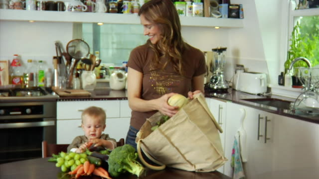 slo mo ms baby boy (6-11 months) assisting mother unloading vegetables and fruits from shopping bag at kitchen counter / london, united kingdom - see other clips from this shoot 1518 stock videos & royalty-free footage