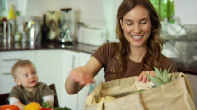 slo mo ms baby boy (6-11 months) assisting mother unloading vegetables from shopping bag at kitchen counter / london, united kingdom - see other clips from this shoot 1518 stock videos & royalty-free footage