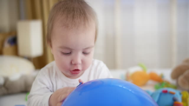 baby boy beißen einen blauen ballon - ein männliches baby allein stock-videos und b-roll-filmmaterial