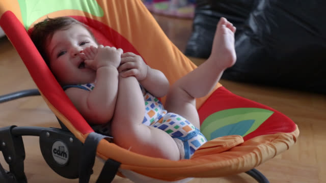 baby boy biting feet while relaxing in baby seat - baby carrier stock videos & royalty-free footage