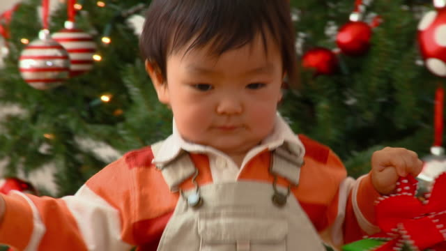 cu, baby boy (12-17 months) carrying present, christmas tree in background, richmond, virginia, usa - babies only stock videos & royalty-free footage