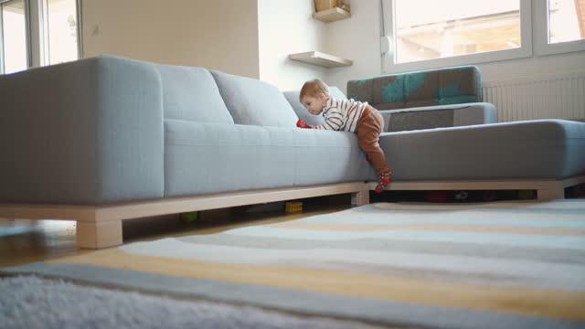 男の子が自分でソファを登り、彼の最初のステップを作る - 男の赤ちゃん一人点の映像素材/bロール