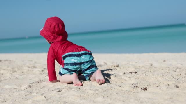 stockvideo's en b-roll-footage met baby boy kruipen op tropisch strand, cayo coco, cuba - zonnehoed hoed