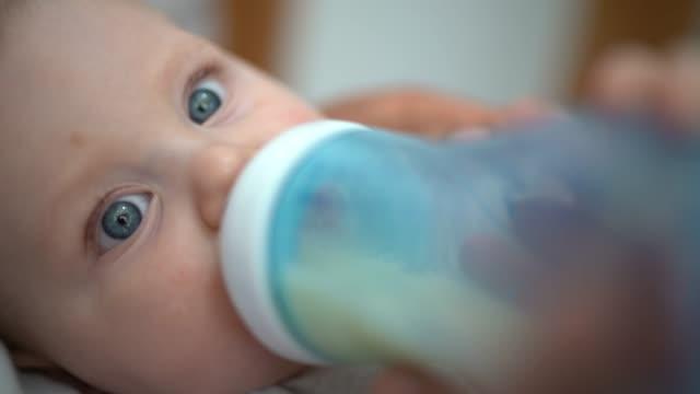 baby boy drinking milk from milk bottle - blue eyes stock videos & royalty-free footage