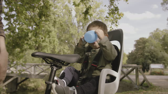 baby boy drinking water from bottle in park sitting in bicycle child seat with father - bicycle seat stock videos & royalty-free footage