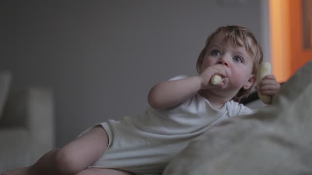 vídeos de stock e filmes b-roll de baby boy eating a banana on a sofa - só um bebé menino