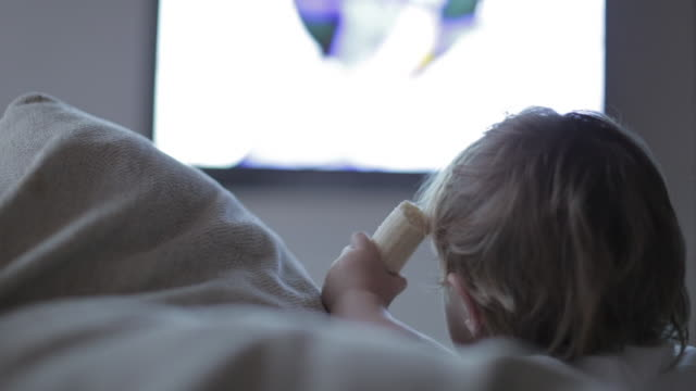baby boy eating a banana watching tv. - in front of stock videos and b-roll footage
