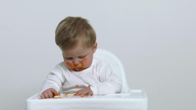 cu baby boy (6-11 months) eating carrot puree / london, uk - ein männliches baby allein stock-videos und b-roll-filmmaterial