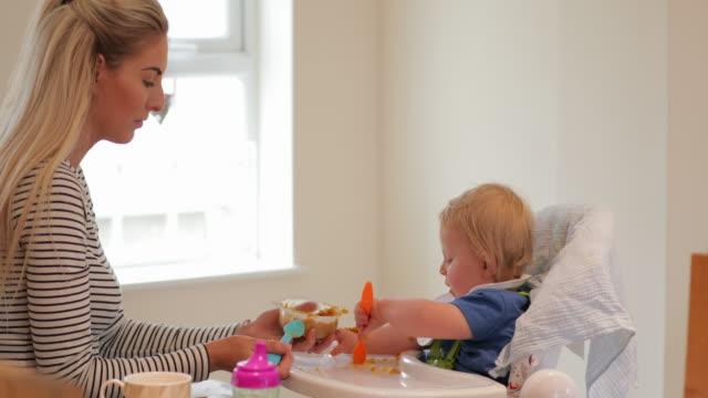 vídeos de stock, filmes e b-roll de menino comendo o jantar com a ajuda de mãe - comida de bebê