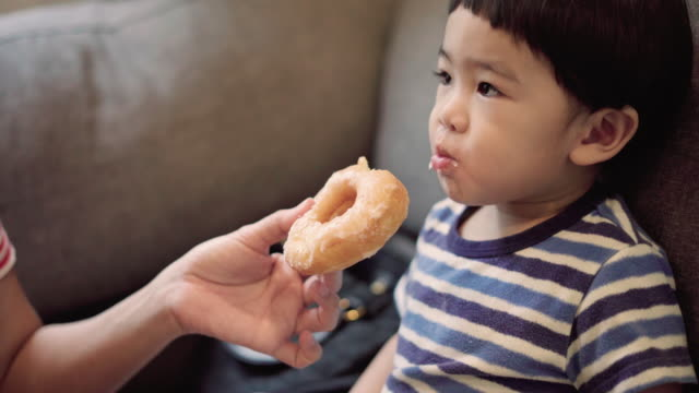 baby boy eating doughnuts with mother - doughnut stock videos & royalty-free footage
