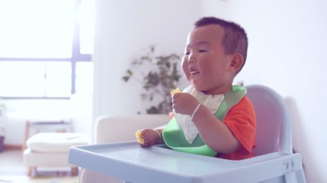 vídeos de stock, filmes e b-roll de menino comendo comida sentado na cadeira alta - só um bebê menino