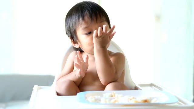 vídeos y material grabado en eventos de stock de niño comiendo en una silla en casa full hd. - sólo niños bebés