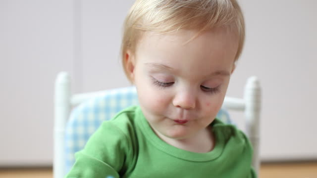 cu baby boy (12-23 months) eating with hands, sitting in high chair / brussels, brabant, belgium - 男の赤ちゃん一人点の映像素材/bロール