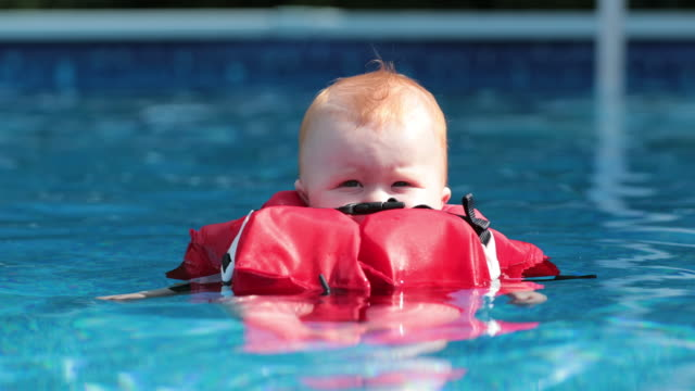 baby boy floating with life jacket in swimming pool - life jacket stock videos & royalty-free footage