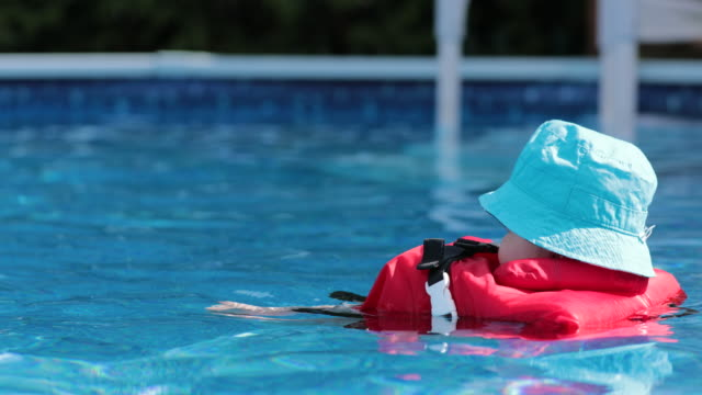 Baby Boy Floating with Life Jacket In Swimming Pool