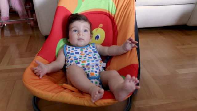 baby boy having fun while laying down in baby seat - baby carrier stock videos & royalty-free footage