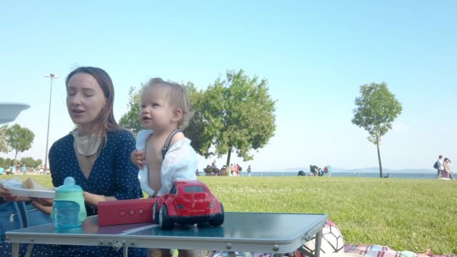 baby boy having picnic with mother in public park - midday stock videos & royalty-free footage