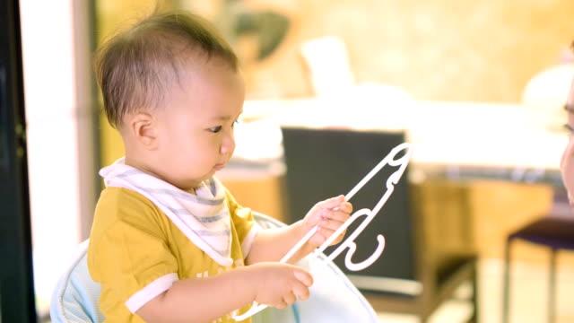 vídeos de stock e filmes b-roll de baby boy helping housework - vestir camiseta