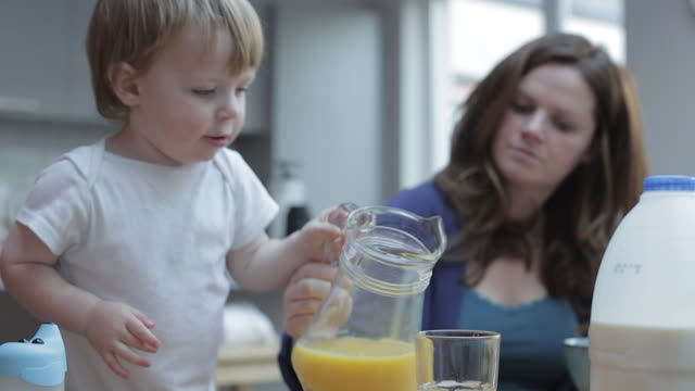 vídeos de stock e filmes b-roll de baby boy helps pour a glass of orange juice - pequeno almoço