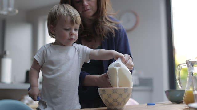 vídeos de stock, filmes e b-roll de baby boy helps pour his own milk - cereal