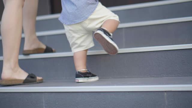 vidéos et rushes de le bébé tient la main de sa mère et marchant sur l'escalier - moving up