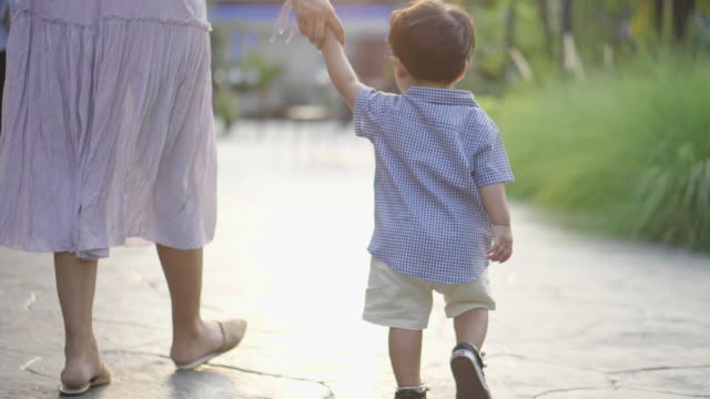 baby boy hold his mother's hand and walking on the staircase - young family stock videos & royalty-free footage