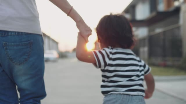 baby boy hold his mother's hand and walking on the street. - young family stock videos & royalty-free footage