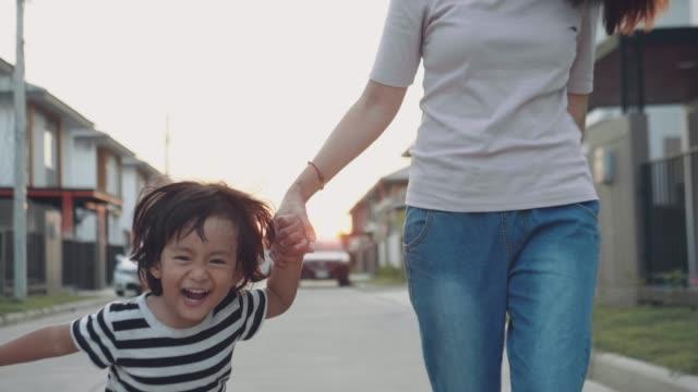 Baby Boy hålla sin mors hand och gå på gatan.