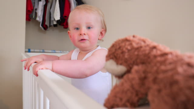 baby boy hugs teddy bear in his crib - soft toy stock videos & royalty-free footage