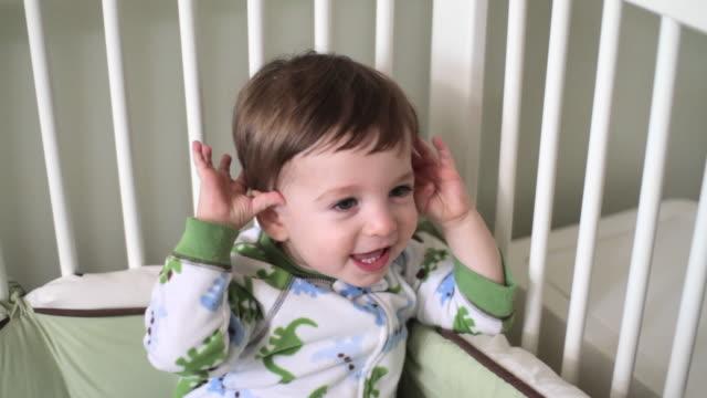 vídeos de stock, filmes e b-roll de baby boy in crib playing peek a boo - só bebês meninos