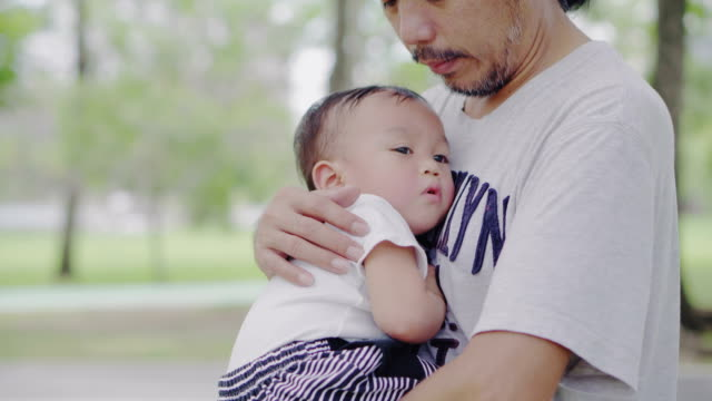baby boy in father's arms - genderblend stock videos & royalty-free footage