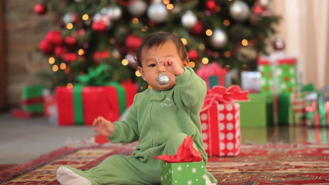 MS Baby boy (6-11 months) in front of Christmas tree playing with bell / Richmond, Virginia, USA