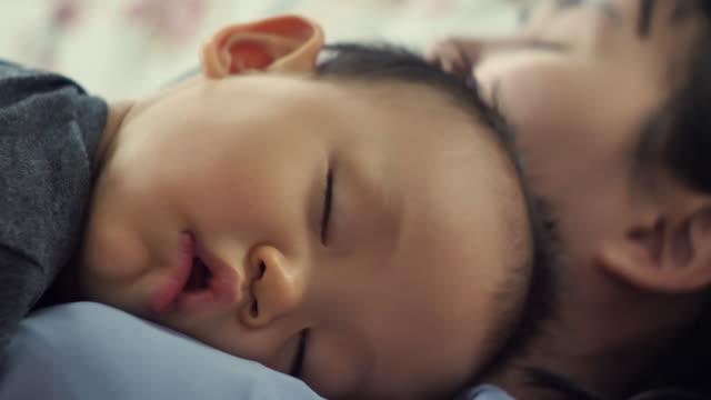 男の子の男の子は寝室で彼の母親の胸の上で眠っています - son点の映像素材/bロール
