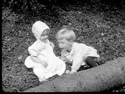 b/w 1920 ms ha baby boy kissing baby girl sitting on grass, pennsylvania, usa - anno 1920 video stock e b–roll
