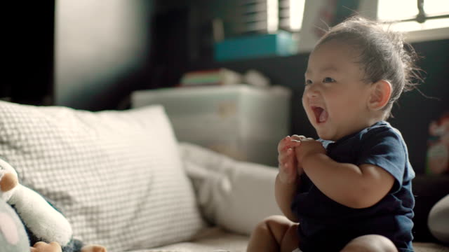 sl a baby boy (6-11 months) laughing and having fun on a bed inside a home. thailand. - nappy stock videos & royalty-free footage