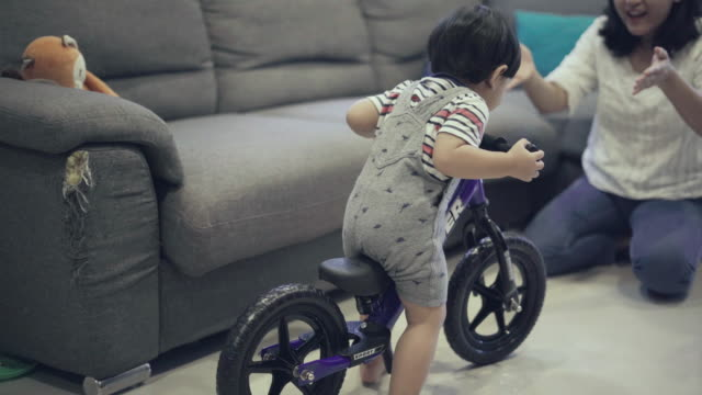 baby boy learn to ride a bike with mother - tricycle stock videos & royalty-free footage