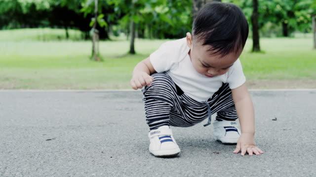 vidéos et rushes de petit garçon, apprendre à marcher dans le parc. - premiers pas