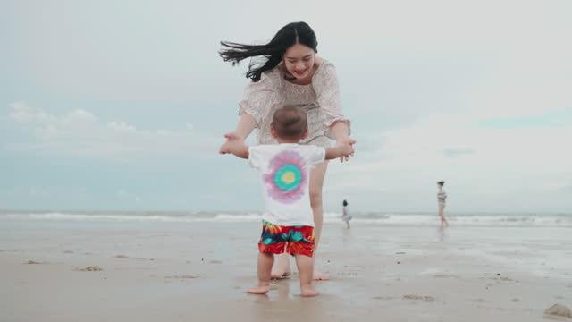 vidéos et rushes de bébé apprenant à marcher enfant en bas âge prenant les premiers pas avec la mère - commencement