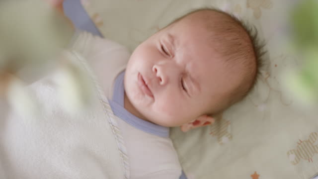 baby boy looking at the mobile above him and sneezing - cute stock videos & royalty-free footage