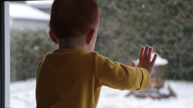 Petit garçon en regardant la fenêtre en hiver