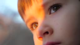 Baby boy looking through window. Kid travels on a train. Teen's face close-up. Rail traffic. Morning sunrise. Traveling by railway. Comfortable train transport. Face reflecting in the glass, window.