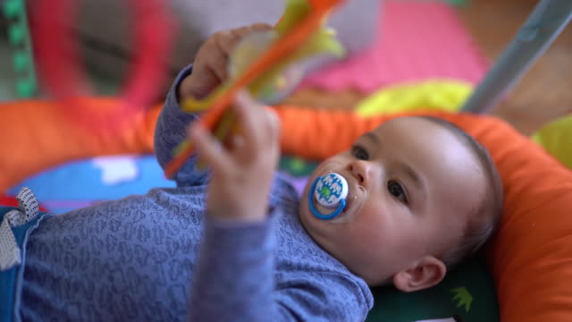 baby boy lying on back and playing with toys - lying on back stock videos & royalty-free footage