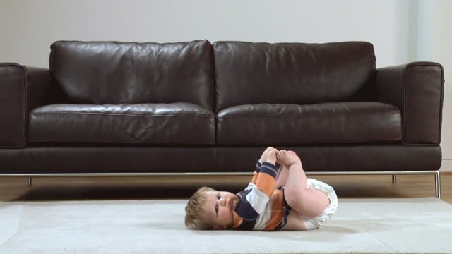 WS Baby boy (6-11 months) lying on carpet playing with his feet / London, UK