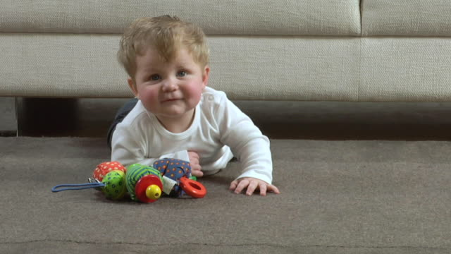 vidéos et rushes de ms baby boy (6-11 months) lying on carpet with toy / london, uk - 6 11 mois