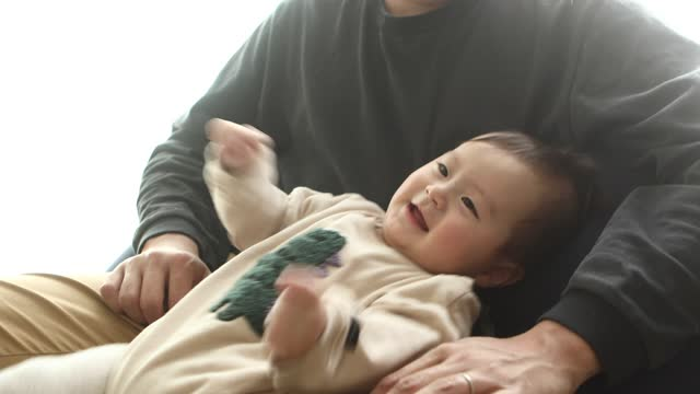 a baby boy moving his body on his father's lap - son点の映像素材/bロール