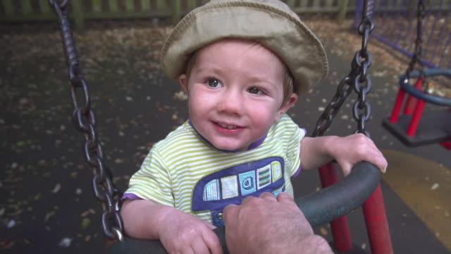 baby boy on park swing - abbigliamento da neonato video stock e b–roll