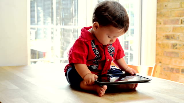 Baby boy on table with tablet
