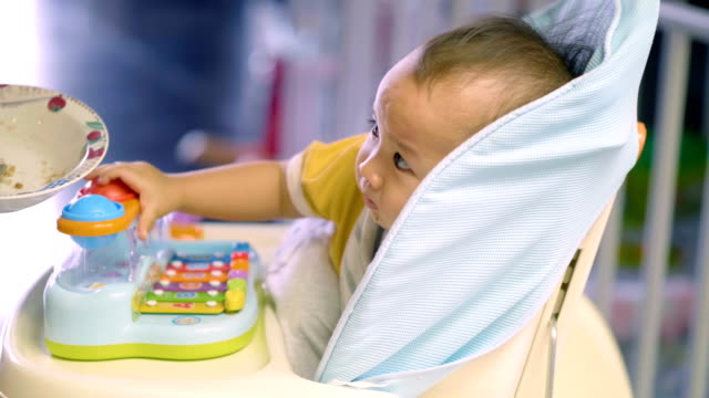 baby boy playing and eating in his chair - soltanto un neonato maschio video stock e b–roll