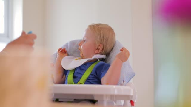 vídeos de stock, filmes e b-roll de baby boy, jogando e comendo na sua cadeira alta - comida de bebê